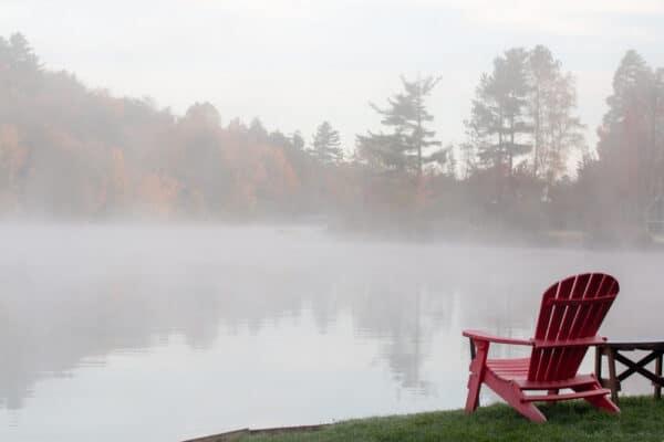 A red Adirondack chair along the shores of Flower Lake in Saranac Lake, NY