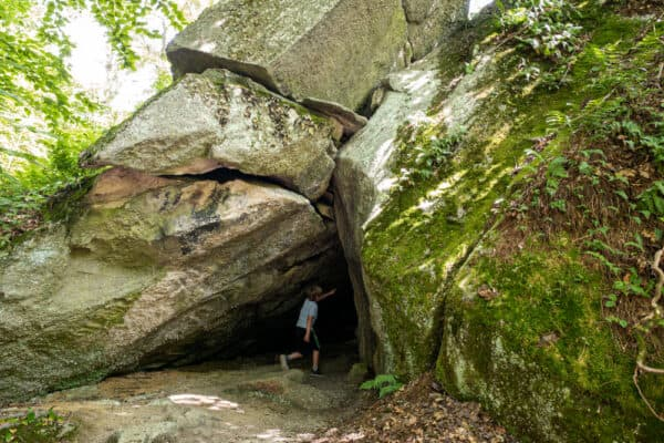 Child entering a cave at Rock City Park in New York