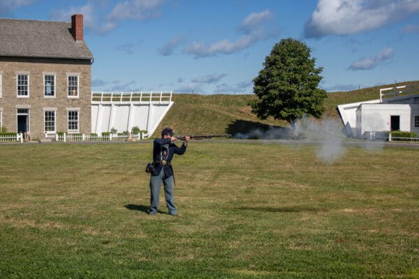 Reenactor firing a gun at Fort Ontario State Historic Site