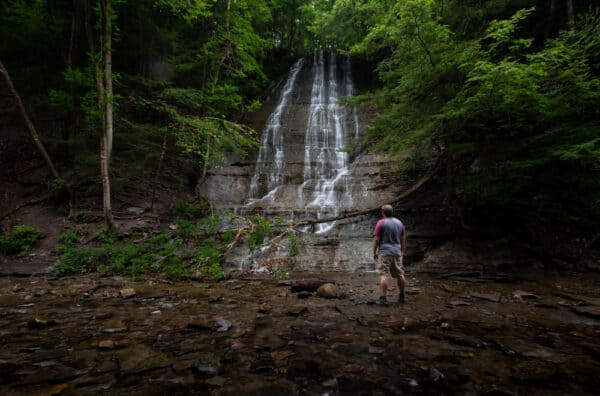 Man in front of waterfall at Grimes Glen in Naples, New York