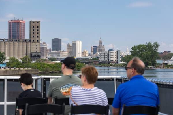 Buffalo skyline behind people sitting on the Buffalo River History Tours