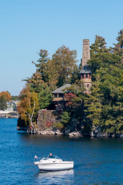 A boat sitting in the water next to an island home in the St. Lawrence River
