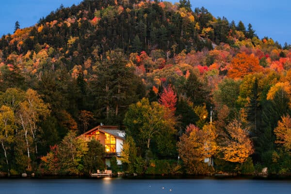 A lakefront cabin sits on a forested hillside in Lake Placid, NY