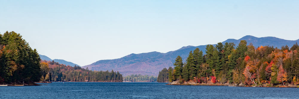A panoramic image of Long Lake with fall foliage in the distance.