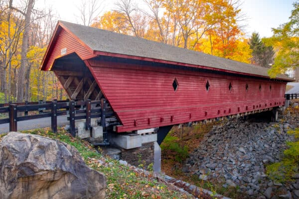 Fall foliage behind Newfield Covered Bridge in Newfield New York